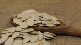 Περιστροφή, σωροί των σπόρων κολοκύθας, που μειώνεται από ένα ξύλινο κουτάλι burlap απόθεμα βίντεο