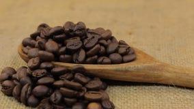 Περιστροφή, σωρός των φασολιών καφέ που πέφτουν από ένα ξύλινο κουτάλι burlap φιλμ μικρού μήκους