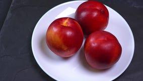 Περιστροφή τριών φρέσκων κόκκινων και κίτρινων ροδάκινων σε πιάτο απόθεμα βίντεο