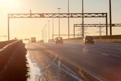 Περιφερειακή οδός πόλεων στο ηλιοβασίλεμα με τις σκιαγραφίες της οδήγησης των αυτοκινήτων Στοκ Φωτογραφίες