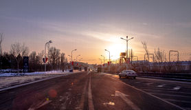 Περιφερειακή οδός πόλεων στο ηλιοβασίλεμα με τις σκιαγραφίες της οδήγησης των οχημάτων Στοκ Φωτογραφία