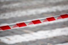 Περιφράζοντας την κόκκινη και άσπρη κορδέλλα που απαγορεύει τη μετακίνηση στοκ εικόνα με δικαίωμα ελεύθερης χρήσης