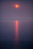 Κόκκινος ήλιος πέρα από τη θάλασσα Στοκ Εικόνες