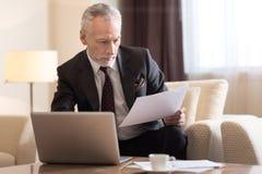 Περιληφθείς επιχειρηματίας που εργάζεται με τα έγγραφα και που κάθεται στο ξενοδοχείο Στοκ φωτογραφία με δικαίωμα ελεύθερης χρήσης