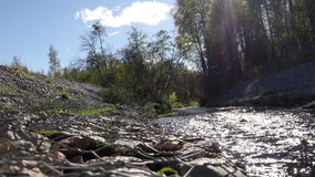 Περνώντας τρεξίματα ποταμών τις πετρώδεις κλίσεις και τη δενδρώδη πράσινη χλόη κάτω από το μπλε ουρανό με τα άσπρα σύννεφα Το παι φιλμ μικρού μήκους