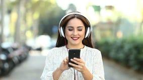 Περπάτημα γυναικών που ακούει στη μουσική σε αργή κίνηση απόθεμα βίντεο