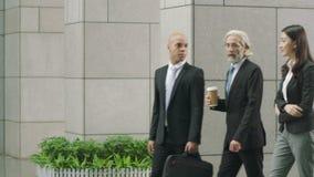 Περπάτημα διοικητικών συνεργατών Multiethnic που μιλά εισάγοντας το σύγχρονο κτήριο