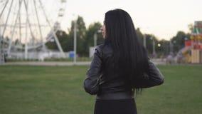 Περπάτημα και στροφές νέων κοριτσιών γύρω στο υπόβαθρο του ηλιόλουστου θερινού πάρκου απόθεμα βίντεο