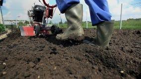 Περπάτημα με τις λαστιχένιες μπότες στο χώμα σε αργή κίνηση απόθεμα βίντεο