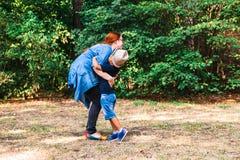 Περπάτημα μητέρων και γιων μαζί υπαίθριο στο ηλιόλουστο πάρκο στοκ φωτογραφία με δικαίωμα ελεύθερης χρήσης