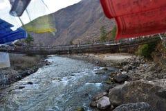 περπάτημα της γέφυρας αναστολής πέρα από τον ποταμό με τις ζωηρόχρωμες σημαίες προσευχής στο Μπουτάν στοκ φωτογραφία