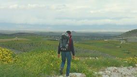 Περπάτημα τουριστών, που απολαμβάνει καταπληκτικός την άποψη της πράσινης κοιλάδας, που εξετάζει τα βουνά φιλμ μικρού μήκους