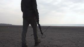 Περπάτημα του επικίνδυνου τέρατος zombie με το βαρύ διαγώνιο τόξο στη χέρσα περιοχή Η έννοια χαρακτήρα φρίκης, που οπλίστηκε και απόθεμα βίντεο