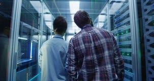 Περπατώντας διαφορετικοί μηχανικοί ΤΠ στο δωμάτιο κεντρικών υπολογιστών φιλμ μικρού μήκους