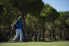 Περπατώντας και φέρνοντας τσάντα φορέων γκολφ Στοκ Φωτογραφία