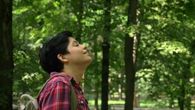 Περπατώντας και χαμογελώντας, πράσινη πάρκων υποβάθρου, ευτυχούς και όμορφης γυναίκα εύθυμων νέων γυναικών σπουδαστών με απότομα  φιλμ μικρού μήκους