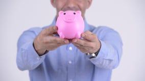 Περσικός επιχειρηματίας που δίνει τη piggy τράπεζα στο άσπρο κλίμα απόθεμα βίντεο