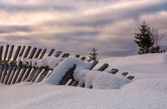 Πεσμένος ξύλινος φράκτης στη χιονώδη βουνοπλαγιά Στοκ Εικόνα