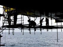 πετρέλαιο βιομηχανίας φ&upsilo Σκιαγραφία των παράκτιων εργαζομένων με την πτώση π Στοκ Φωτογραφία