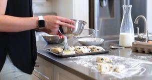 Πετρέλαιο βουρτσίσματος γυναικών στη ζύμη μπισκότων σε kitchen4k απόθεμα βίντεο
