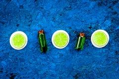 Πετρέλαιο εσπεριδοειδών με το λεμόνι ή ασβέστης για το aromatheraphy ή τη φροντίδα δέρματος στο μπλε διάστημα αντιγράφων άποψης υ Στοκ Φωτογραφίες