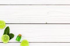 Πετρέλαιο εσπεριδοειδών με το λεμόνι ή ασβέστης για το aromatheraphy ή τη φροντίδα δέρματος στο άσπρο ξύλινο διάστημα αντιγράφων  Στοκ Εικόνα