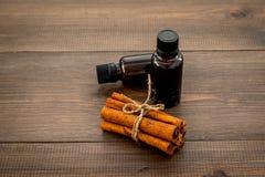 Πετρέλαιο κανέλας για το μαγείρεμα, aromatheraphy, φροντίδα δέρματος Μπουκάλια κοντά στα ραβδιά κανέλας στο σκοτεινό ξύλινο υπόβα Στοκ εικόνα με δικαίωμα ελεύθερης χρήσης