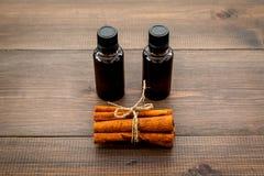 Πετρέλαιο κανέλας για το μαγείρεμα, aromatheraphy, φροντίδα δέρματος Μπουκάλια κοντά στα ραβδιά κανέλας στο σκοτεινό ξύλινο διάστ Στοκ φωτογραφίες με δικαίωμα ελεύθερης χρήσης