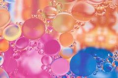 Πετρέλαιο που αναμιγνύεται με το νερό σε ένα χρωματισμένο υπόβαθρο στοκ εικόνες
