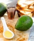 Πετρέλαιο αβοκάντο σε ένα κουτάλι και ένα φρέσκο πράσινο αβοκάντο Στοκ Φωτογραφία