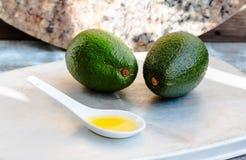 Πετρέλαιο αβοκάντο σε ένα κουτάλι και ένα φρέσκο πράσινο αβοκάντο Στοκ Εικόνες
