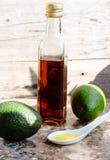 Πετρέλαιο αβοκάντο σε ένα μπουκάλι γυαλιού και ένα φρέσκο πράσινο αβοκάντο Στοκ Φωτογραφία