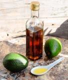 Πετρέλαιο αβοκάντο σε ένα μπουκάλι γυαλιού και ένα φρέσκο πράσινο αβοκάντο Στοκ Εικόνα