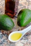 Πετρέλαιο αβοκάντο σε ένα μπουκάλι γυαλιού και ένα φρέσκο πράσινο αβοκάντο Στοκ Φωτογραφίες