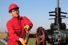 Πετρέλαιο και φυσικό αέριο που τρυπούν καλά τον εργαζόμενο με τρυπάνι Στοκ Φωτογραφία