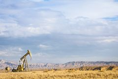 Πετρελαιοπηγή με τον ουρανό και το υπόβαθρο βουνών Στοκ Φωτογραφίες