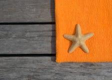 Πετσέτα και αστερίας παραλιών στο ξύλινο υπόβαθρο Στοκ εικόνες με δικαίωμα ελεύθερης χρήσης