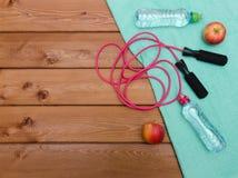 Πετσέτα, μήλα μπουκαλιών νερό και πηδώντας σχοινί στον ξύλινο πίνακα Στοκ Εικόνες