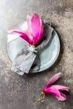 Πετσέτα με το λουλούδι magnolia στο γκρίζο πιάτο, υπόβαθρο πετρών Τοπ όψη Στοκ Φωτογραφία