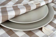 Πετσέτα στο μπεζ καρό και τα γκρίζα πιάτα Πετσέτα και πιάτα κουζινών Στοκ φωτογραφίες με δικαίωμα ελεύθερης χρήσης