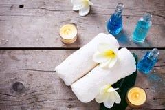 Πετσέτες, μπουκάλια με το πετρέλαιο και το άσπρο λουλούδι plumeria στο ξύλινο β Στοκ φωτογραφίες με δικαίωμα ελεύθερης χρήσης