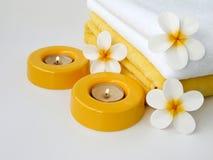 Πετσέτες, δύο κεριά και λουλούδια frangipani Στοκ Φωτογραφία