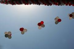 Πετώντας ζωηρόχρωμα μπαλόνια ενάντια στο μπλε ουρανό Πολυ χρωματισμένη γιρλάντα των μπαλονιών Μια όμορφη διακόσμηση για ένα φεστι Στοκ Εικόνες