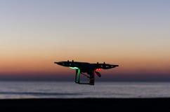 Πετώντας κηφήνας με τη κάμερα στον ουρανό στο ηλιοβασίλεμα Στοκ Φωτογραφίες
