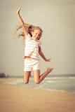 Πετώντας κορίτσι παραλιών άλματος στην μπλε ακροθαλασσιά Στοκ Φωτογραφίες