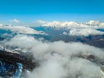 Πετώντας πέρα από τα χιονώδη βουνά, το ίχνος δασών και σκι στην ομίχλη Στοκ Εικόνες
