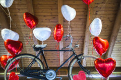Πετώντας παλαιό ποδήλατο που δεσμεύεται διαμορφωμένα στα καρδιά μπαλόνια Στοκ εικόνα με δικαίωμα ελεύθερης χρήσης