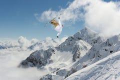 Πετώντας σκιέρ στα χιονώδη βουνά Ακραίος χειμερινός αθλητισμός, αλπικό σκι στοκ εικόνες