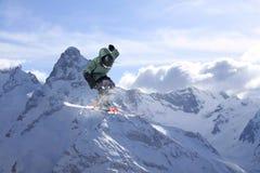 Πετώντας σκιέρ στα χιονώδη βουνά Ακραίος χειμερινός αθλητισμός, αλπικό σκι στοκ φωτογραφίες