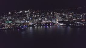 Πετώντας στην πόλη τη νύχτα, πέρα από το λιμάνι που απεικονίζει το νερό 4k απόθεμα βίντεο